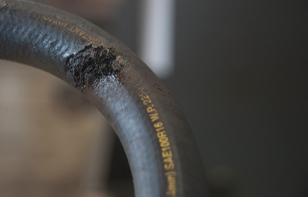 A damaged hydraulic hose was removed from a dump truck March 13, 2017, at Kadena Air Base, Japan. Scuffs, scratches and continues rubbing, paired with incredibly high pressure per square inch, can lead to dangerous hydraulic line failure. The 18th Logistics Readiness Squadron takes care to ensure that these machines are not out of service long, keeping the Kadena mission moving forward. (U.S. Air Force photo by Airman 1st Class Quay Drawdy)