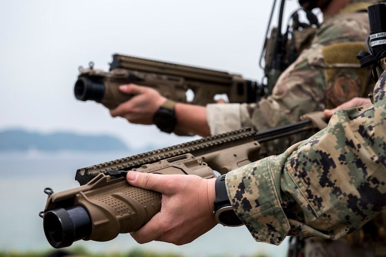 A U.S. Air Force combat controller from the 320th Special Tactics Squadron, and a Marine joint terminal attack controller from the 5th Air Naval Gunfire Liaison Company, III Marine Expeditionary Force, wield 40 mm grenade launchers during a training exercise March 10, 2017, at the Irisuna Jima Training Range, Okinawa, Japan. The launchers are used to shoot out smoke grenades as a visual marker for friendly aircraft. (U.S. Air Force photo by Senior Airman John Linzmeier)