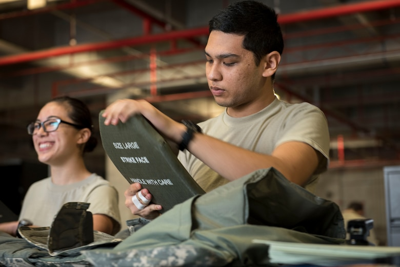 U.S. Air Force Airman 1st Class James Salas, 18th Logistics Readiness Squadron material management technician, inspects a ballistic insert March 13, 2017, at Kadena Air Base, Japan. The IPE Shop is the first line of defense for Airmen, ensuring protective gear is supplied and functions properly. (U.S. Air Force photo by Senior Airman John Linzmeier)