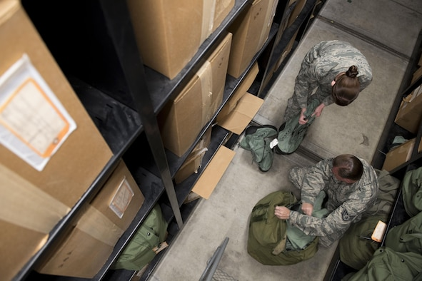 U.S. Air Force material management technicians from the 445th Logistics Readiness Squadron, inspect  ndividual protective equipment March 13, 2017, at Kadena Air Base, Japan. The Airmen are temporarily embedded in the 18th LRS IPE shop to help organize, keep inventory, test and inspect deployment and training gear. (U.S. Air Force photo by Senior Airman John Linzmeier)