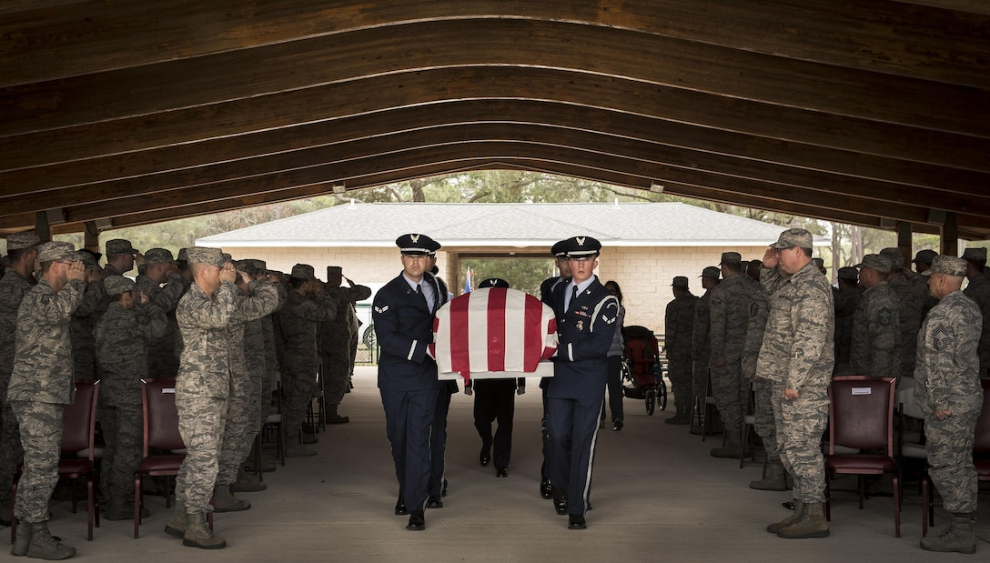 People in attendance salute as the casket, carried by Eglin Honor Guard, passes by during the unit's graduation ceremony at Eglin Air Force Base, Fla., March 1.  Approximately 12 new Airmen graduated from the 120-plus-hour course. The graduation performance includes flag detail, rifle volley, pall bearers and bugler for friends, family and unit commanders. (U.S. Air Force photo/Samuel King Jr.)