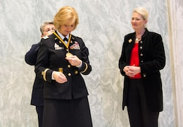 Retired Command Sgt. Maj. Cindy Pritchett places a medal around Chief Warrant Officer 5 Phyllis Wilson's neck, while retired Brig. Gen. Anne MacDonald looks on, as Wilson is inducted at the U.S. Army Women's Foundation Hall of Fame Induction ceremony in Washington, D.C., on March 8, 2017.  MacDonald is the president of the USAWF.