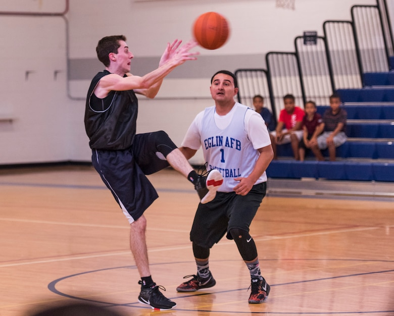 Bryan Wilson, Armament Directorate, passes the ball past Santos Padilla, 53rd Wing, during the intramural basketball championship March 6 at Eglin Air Force Base Fla. The EB team defeated the 53rd Wing team 53-42 to take the trophy. (U.S. Air Force photo/Ilka Cole)