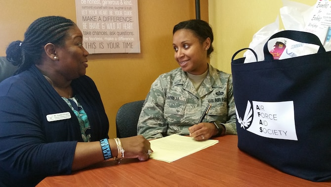 Tech. Sgt. Joy Garrett, 96th Force Support Squadron, fills out paperwork for Air Force Aid Society assistance as Suzette Ellington, AFAS officer, looks on.  The Air Force Aid Society's 75th anniversary was March 9.  (U.S. Air Force photo/Kevin Gaddie)