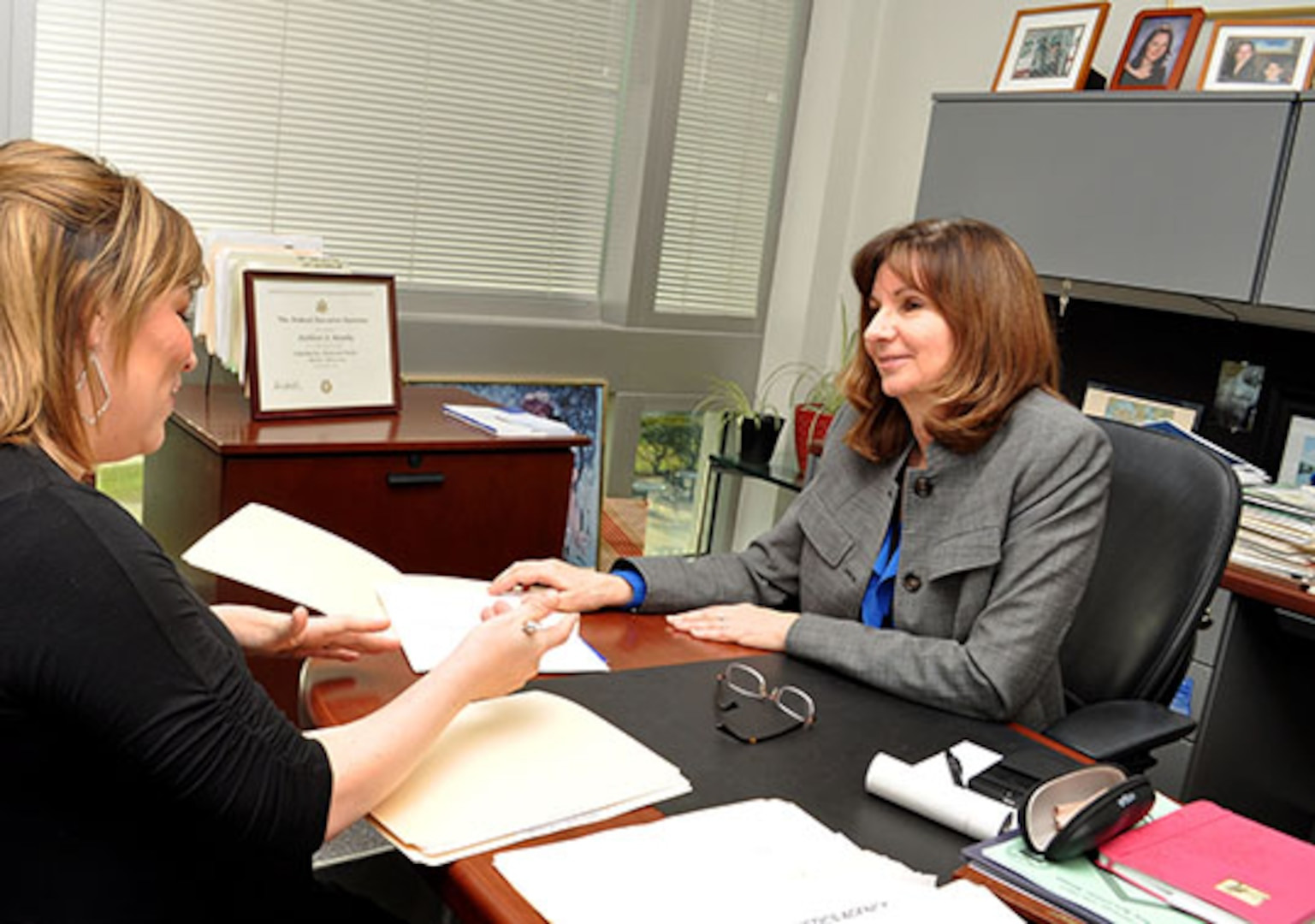 DLA Energy Chief Counsel Kathleen Murphy, right, guides mentee, Heather Thomas, a contract specialist with Utility Services Contracting Branch II.
