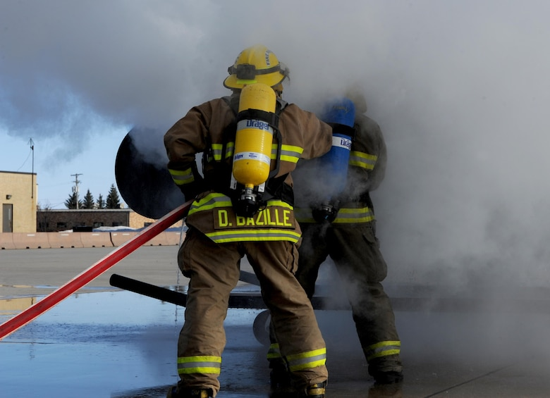 Dustin Bazille, Kenmore fire department firefighter, and Tim McCartney North Lemmon fire department firefighter, put out a simulated fire at Minot Air Force Base, N.D., Feb. 24, 2017. Bazille and McCartney trained with the Minot AFB fire department, which included several training events with a final simulated helicopter fire on the flight line. (U.S. Air Force photo/Staff Sgt. Chad Trujillo)