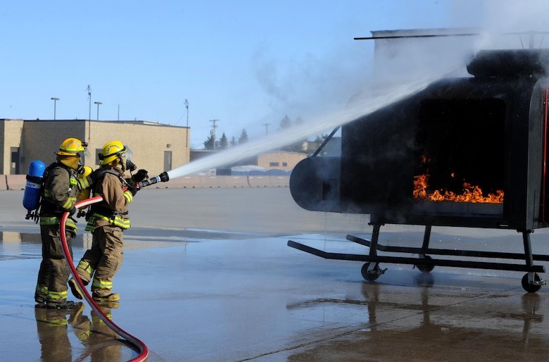 Dustin Bazille, Kenmore fire department firefighter, and Tim McCartney North Lemmon fire department firefighter, put out a simulated fire at Minot Air Force Base, N.D., Feb. 24, 2017. The Minot AFB fire department hosted training with local fire departments, scenarios included simulated helicopter fire and missile field response. (U.S. Air Force photo/Staff Sgt. Chad Trujillo)