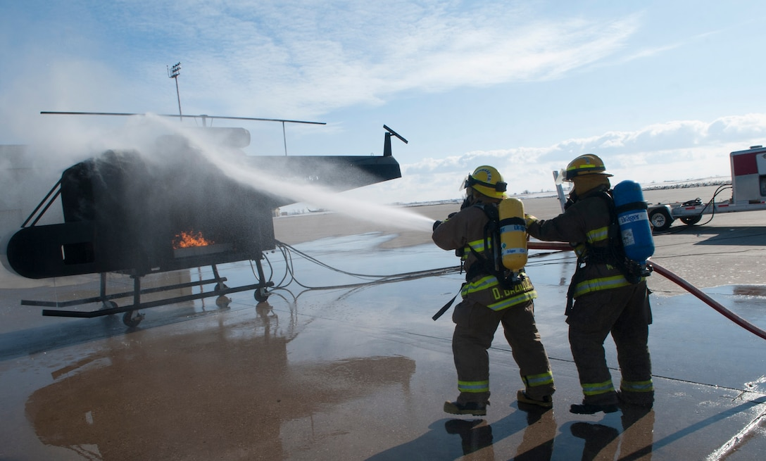 (From left) Dustin Bazille, Kenmare Fire Department firefighter, and Tim McCartney, North Lemmon Fire Department firefighter, spray water onto a mobile trainer at Minot Air Force Base, N.D., Feb. 24, 2017. The 5th Civil Engineer fire department invited several local fire departments for missile field response training. (U.S. Air Force photo/Airman 1st Class Jonathan McElderry)