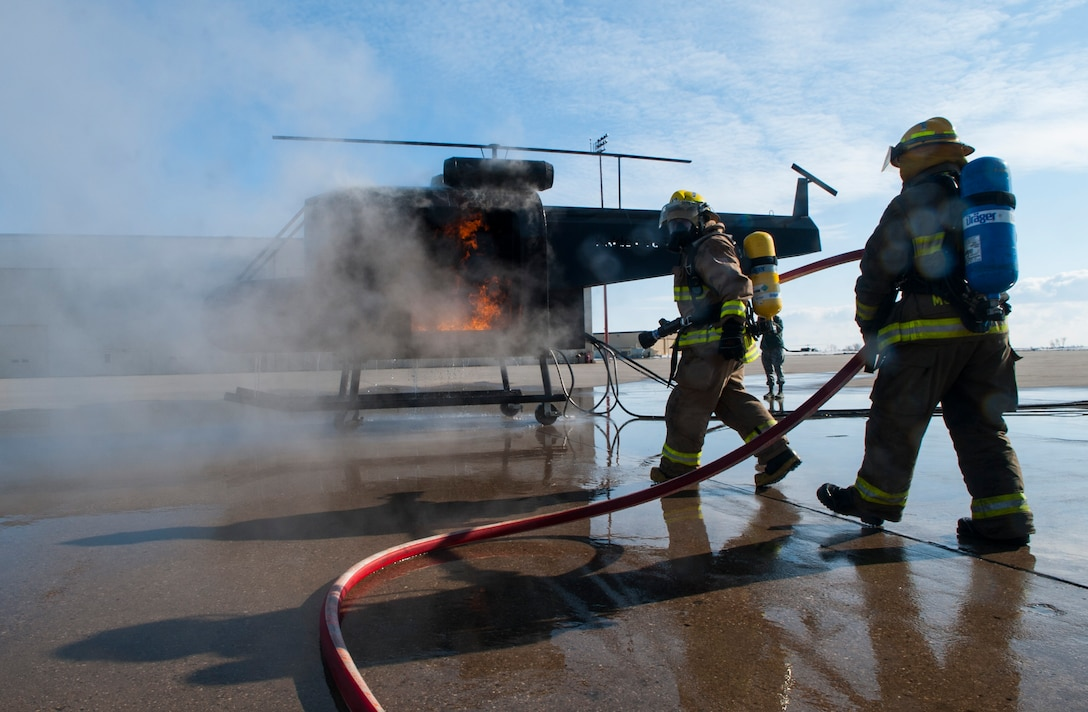 (From left) Dustin Bazille, Kenmare Fire Department firefighter, and Tim McCartney, North Lemmon Fire Department firefighter, extinguish a burning mobile trainer at Minot Air Force Base, N.D., Feb. 24, 2017. The Minot AFB 5th Civil Engineer Squadron hosted a North Dakota Fire Association training class for mutual aid fire departments. (U.S. Air Force photo/Airman 1st Class Jonathan McElderry)