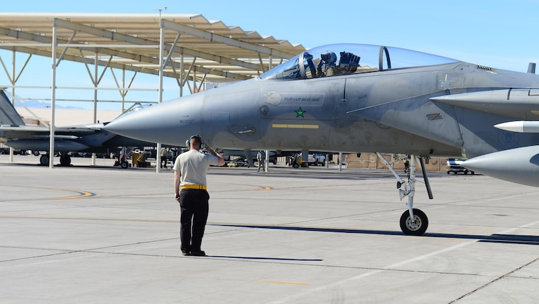 A 493rd Aircraft Maintenance Unit Airman from Royal Air Force Lakenheath, England, marshals out an F-15C Eagle for exercise Red Flag 17-2 at Nellis Air Force Base, Nev., Mar. 3. More than 30 countries have participated directly in a Red Flag exercise. (U.S. Air Force photo/Senior Airman Malcolm Mayfield)