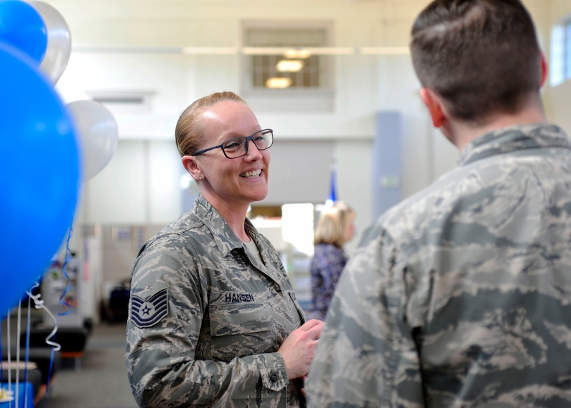 Tech. Sgt. Nalopa Hansen, 627th Force Support Squadron Air Force Aid Society assistant officer, smiles while speaking to a fellow Airman during the AFAS 75th Anniversary Celebration, March 10, 2017 at the Military Personnel Section on McChord Field, Wash. As their website proudly proclaims, for every dollar donated, AFAS pledges to provide three dollars to Airmen in need. (U.S. Air Force photo/Staff Sgt. Whitney Amstutz)