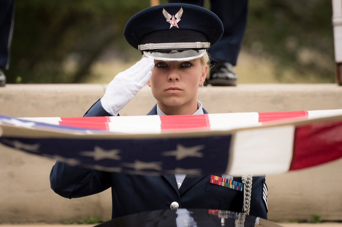 Staff Sgt. Elena Konter, 96th Medical Operations Squadron, salutes during the flag-folding portion of the unit's graduation ceremony at Eglin Air Force Base, Fla., March 1.  Approximately 12 new Airmen graduated from the 120-plus-hour course. The graduation performance includes flag detail, rifle volley, pall bearers and bugler for friends, family and unit commanders. (U.S. Air Force photo/Samuel King Jr.)