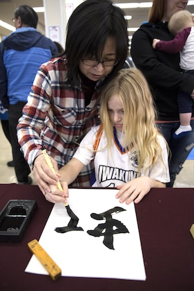 "A local Japanese volunteer for the Japanese American Society teaches an American child how to write ""Rainbow"" in calligraphy during the 60th Annual Culture Festival at Marine Corps Air Station Iwakuni, Japan, March 11, 2017. The festival included Japanese dance performances, decorated exhibits and traditional activities and rituals. JAS continues to bridge the U.S.-Japan friendship by providing quality cultural events and activities. (U.S. Marine Corps photo by Lance Cpl. Carlos Jimenez)"