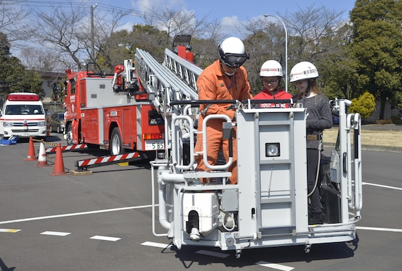 A member of the Tokyo Fire Department shows Yokota West Elementary School students what it's like to be in a ladder basket during the Yokota Safety and Readiness Festival at Yokota Air Base, Japan, March 10, 2017. The event allowed Yokota personnel to have fun while learning how to safely handle situations that could take place in their daily lives. (U.S. Air Force photo by Staff Sgt. David Owsianka)