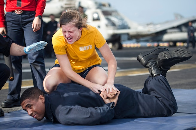 Navy Ensign Jayne Woolard performs a mechanical advantage control hold on Navy Petty Officer 3rd Class Matthew Alexander after being sprayed with oleoresin capsicum spray during naval security force sentry training aboard the amphibious assault ship USS Makin Island at sea, March 4, 2017. The ship is deployed in the U.S. 5th Fleet area of operations in support of maritime security operations designed to reassure allies and partners, and preserve the freedom of navigation and the free flow of commerce in the region. Navy photo by Petty Officer 3rd Class Devin M. Langer