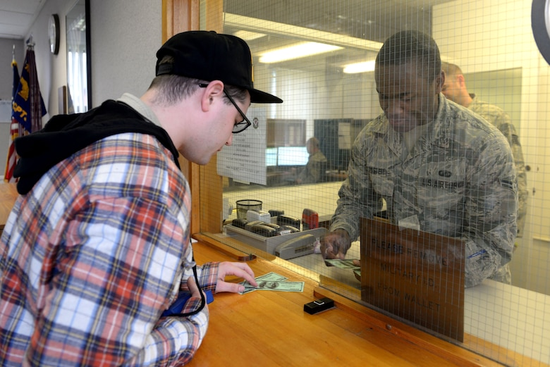U.S. Air Force Senior Airman Ryan Hanlon, 100th Security Forces Squadron electronic security system manager, simulates robbing the 100th Comptroller Squadron cash cage from U.S. Air Force Airman 1st Class Shaquille Simister, 100th CPTS financial services apprentice, March 13, 2017, on RAF Mildenhall, England. The simulated armed robbery was part of an exercise to test 100th CPTS Airmen under pressure and ensure they're ready in case of a real-world incident. (U.S. Air Force photo by Staff Sgt. Kate Thornton)