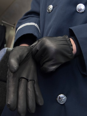 Airman 1st Class Daniela Bejarano, U.S. Air Force Honor Guard ceremonial guardsman, puts on gloves in preparation for the annual Chicago St. Patrick's Day Parade, March 11, 2017. In addition to wearing gloves, the honor guard members wore overcoats, earmuffs, a scarf and black sling to combat winter temperatures of less than 30 degrees during the event. (U.S. Air Force photo by Senior Airman Jordyn Fetter)
