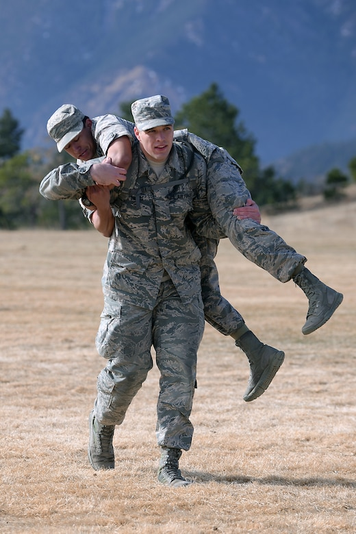 """A freshman cadet at the U.S. Air Force Academy, Colorado,uses the """"fireman's carry"""" to carry another freshman March 10, 2017 during Recognition. Recognition is a rigorous annual event freshmen or """"four degrees"""" must overcome before earning the title of cadet. (U.S. Air Force photo/Darcie Ibidapo)"""