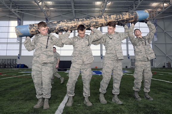 "Freshmen cadets hold up a heavy log during Recognition, March 10, 2017, at the U.S. Air Force Academy, Colorado. Recognition is a rigorous annual event freshmen or ""four degrees"" must overcome before earning the status of ""recognized cadet."" (U.S. Air Force photo/Jason Gutierrez)"