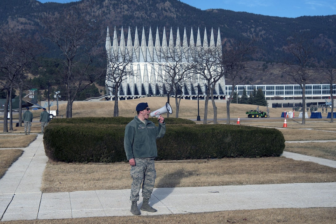 "A senior cadet at the U.S. Air Force Academy, Colorado, uses a megaphone to get the attention of freshmen cadets March 10, 2017 during Recognition. Recognition is a rigorous annual event freshmen or ""four degrees"" must overcome before earning the status of ""recognized cadet"" at the Academy.  (U.S. Air Force photo/Bill Evans)"