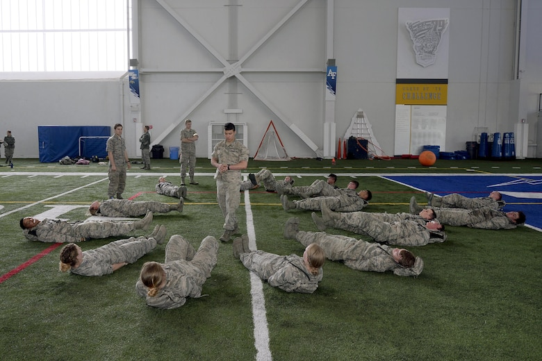 """A senior cadets leads freshmen cadets through flutter kicks March 10, 2017 at the U.S. Air Force Academy, Colorado, during Recognition. Recognition is a rigorous annual event freshmen or """"four degrees"""" must overcome before earning the status of """"recognized cadet."""" (U.S. Air Force photo/Jason Gutierrez)"""
