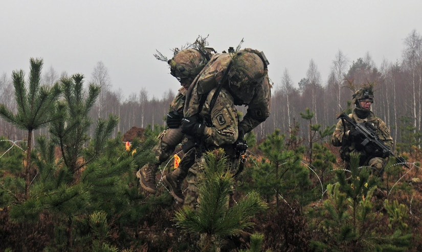 "A soldier from Able Company, 2nd Battalion, 503rd Infantry Regiment, carries a ""wounded"" comrade off the battlefield during Iron Sword 2016 in Pabrade, Lithuania, Nov. 24, 2016. The exercise is designed to promote regional stability and security while strengthening partner capacity. Army photo by Staff Sgt. Corinna Baltos"