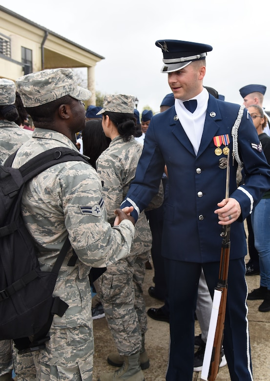Airman 1st Class Emmanuel Agyemang Duah, 335th Training Squadron student, meets Airman 1st Class Caleb Gothard, U.S. Air Force Honor Guard Drill Team member, following the debut performance of the team's 2017 routine during the 81st Training Group drill down at the Levitow Training Support Facility drill pad March 10, 2017, on Keesler Air Force Base, Miss. The team comes to Keesler every year for five weeks to develop a new routine that they will use throughout the year. (U.S. Air Force photo by Kemberly Groue)