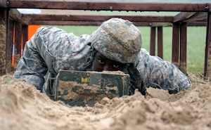 Spec. Gregory Stephens, JBSA-Fort Sam Houston Dental Activity, low crawls during one of 16 obstacle events during the Regional Best Warrior Competition hosted by the Joint Base San Antonio-Fort Sam Houston Dental Health Activity, or DENTAC, from Feb. 27 to March 3 at JBSA-Camp Bullis.