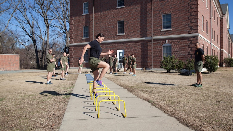 Staff Sgt. Robyn Czuri, a faculty advisor at the Marine Corps Base Quantico Staff Noncommissioned Officer Academy, demonstrates correct form for an exercise drill during physical training at MCB Quantico, Virginia, Mar. 8, 2017. Enlisted Marines come to Quantico in order to be qualified and teach as a faculty advisor, a role that helps facilitate hundreds of Marines a year in their resident professional military education.
