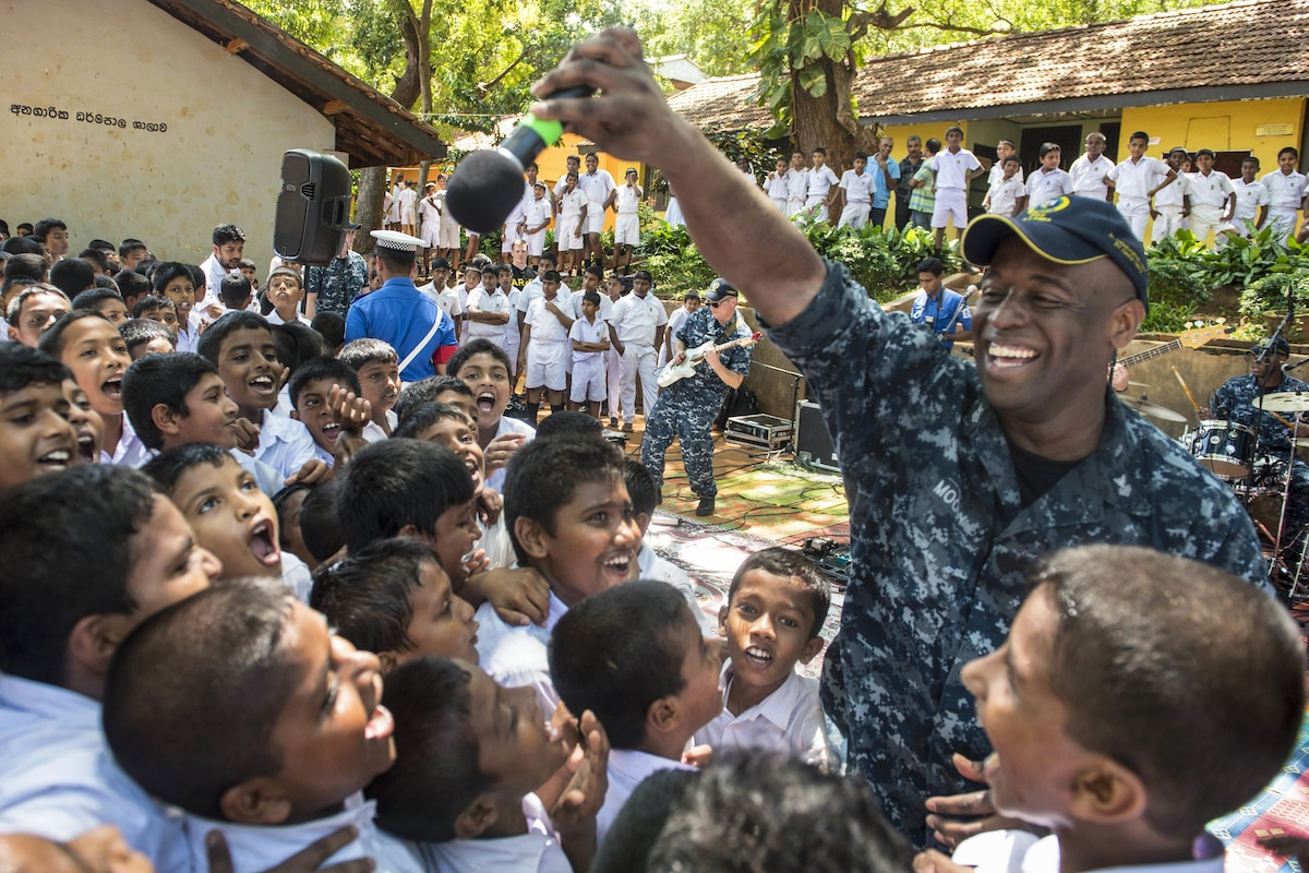 A sailor sings to children who surround him and smile.