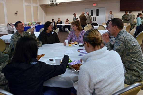 Maggie Catoe, 20th Medical Support Squadron key spouse mentor, center left, speaks with individuals from her squadron during a pre-deployment dinner at the Carolina Skies and Conference Center at Shaw Air Force Base, S.C., March 13, 2017. Key spouses help welcome families to Team Shaw and act as liaisons between spouses and helping agencies. (U.S. Air Force photo by Airman 1st Class Destinee Sweeney)