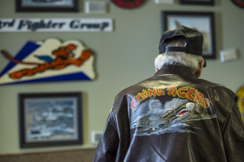J.M. Taylor, World War II veteran and prisoner of war, looks at a heritage display during the 75th Anniversary Flying Tiger Reunion, March 10, 2017, at Moody Air Force Base, Ga. In 1941, President Roosevelt signed an executive order forming the American Volunteer Group. The AVG was organized into the 1st, 2nd, and 3rd Pursuit Squadrons and later disbanded and replaced by the 23d Fighter Group in 1942. Under the command of Gen. Claire Chennault, the Flying Tigers comprised of the 74th, 75th, and 76th Pursuit Squadrons defended China against the Japanese. Throughout World War II, the Flying Tigers achieved combat success and flew the US-made Curtiss P-40 Warhawks painted with the shark-mouth design. (U.S. Air Force photo by Senior Airman Ceaira Young)