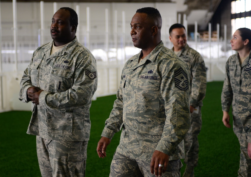 Staff Sgt. Adrian Banks, the Bellamy Fitness Center facility supervisor assigned to the 28th Force Support Squadron, escorts Chief Master Sgt. Calvin Williams, Air Force Global Strike Command command chief, through the Pride Hangar during a visit to Ellsworth Air Force Base, S.D., March 2, 2017. Banks explained the recent updates to the Pride Hangar, including a new indoor soccer field, batting areas and improved lighting. (U.S. Air Force photo by Airman 1st Class Denise M. Jenson)
