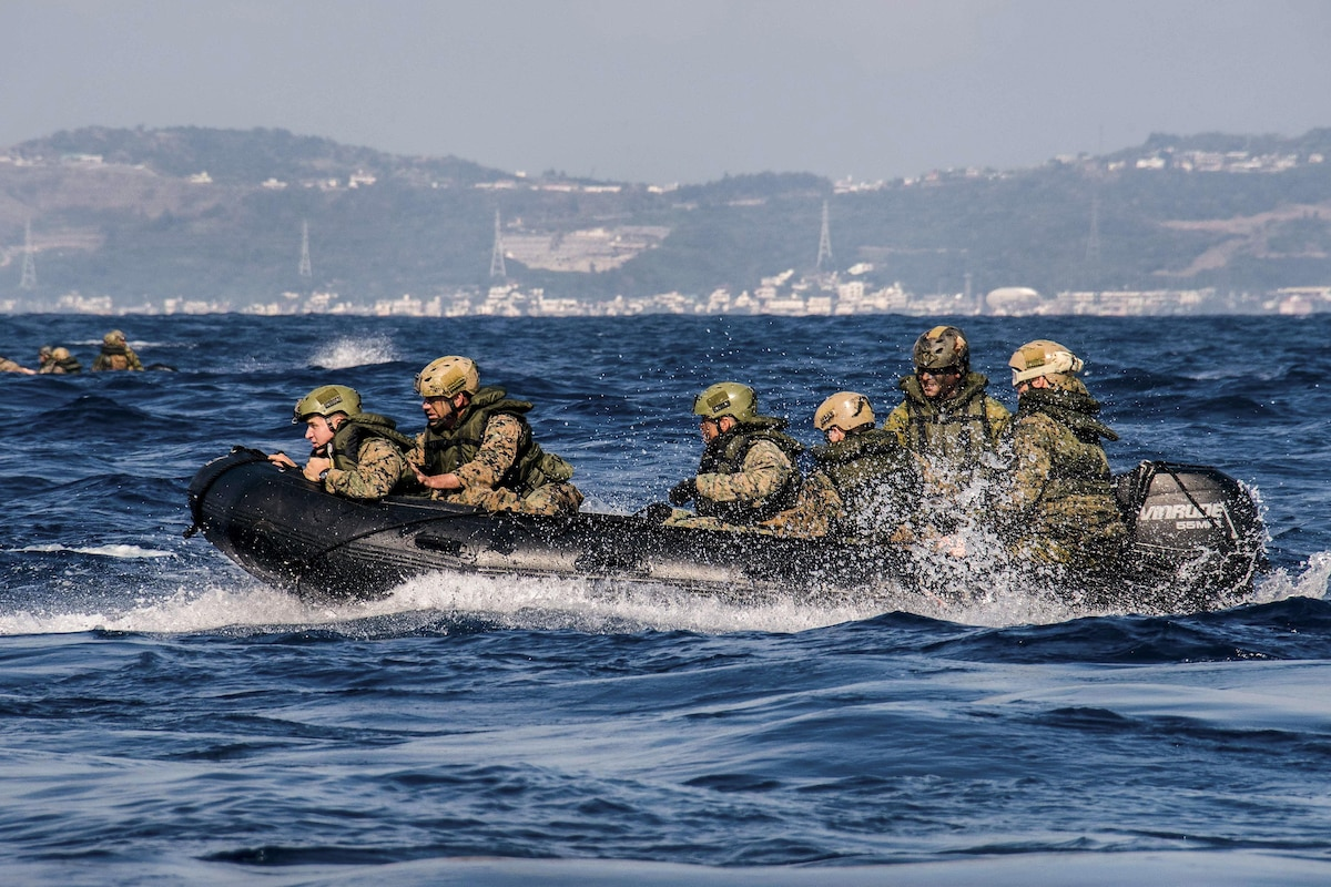 Marines ride in a rubber raiding craft.