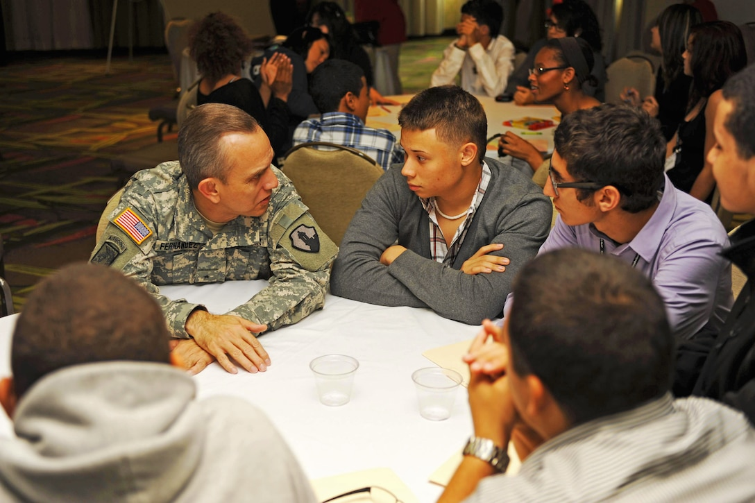 Army Brig. Gen. Fernando Fernández talks with several teenagers