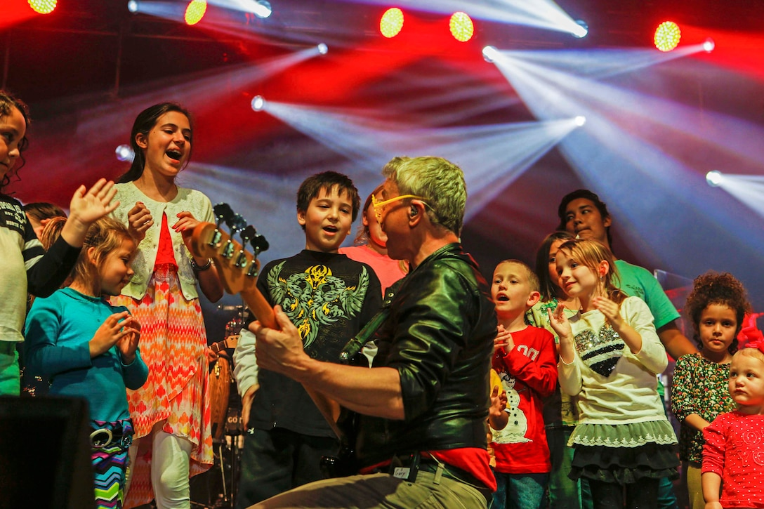 Gary Sinise, electric bassist, interacts with children on stage