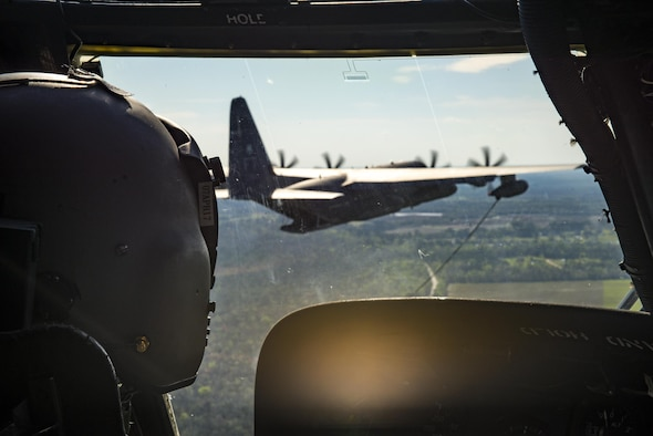 An HH-60G Pave Hawk pilot from the 41st Rescue Squadron flies towards an HC-130J Combat King II as part of a refueling demonstration during the 75th Anniversary Flying Tiger Reunion, March 10, 2017, at Moody Air Force Base, Ga. In 1941, President Roosevelt signed an executive order forming the American Volunteer Group. The AVG was organized into the 1st, 2nd, and 3rd Pursuit Squadrons and later disbanded and replaced by the 23d Fighter Group in 1942. Under the command of Gen. Claire Chennault, the Flying Tigers comprised of the 74th, 75th, and 76th Pursuit Squadrons defended China against the Japanese. Throughout World War II, the Flying Tigers achieved combat success and flew the US-made Curtiss P-40 Warhawks painted with the shark-mouth design. (U.S. Air Force photo by Staff Sgt. Ryan Callaghan)