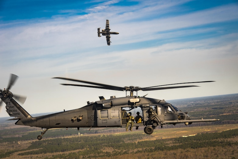 An A-10C Thunderbolt II from the 23d Fighter Group escorts an HH-60G Pave Hawk as part of a combat search and rescue demonstration during the 75th Anniversary Flying Tiger Reunion, March 10, 2017, at Moody Air Force Base, Ga. In 1941, President Roosevelt signed an executive order forming the American Volunteer Group. The AVG was organized into the 1st, 2nd, and 3rd Pursuit Squadrons and later disbanded and replaced by the 23d Fighter Group in 1942. Under the command of Gen. Claire Chennault, the Flying Tigers comprised of the 74th, 75th, and 76th Pursuit Squadrons defended China against the Japanese. Throughout World War II, the Flying Tigers achieved combat success and flew the US-made Curtiss P-40 Warhawks painted with the shark-mouth design. (U.S. Air Force photo by Staff Sgt. Ryan Callaghan)