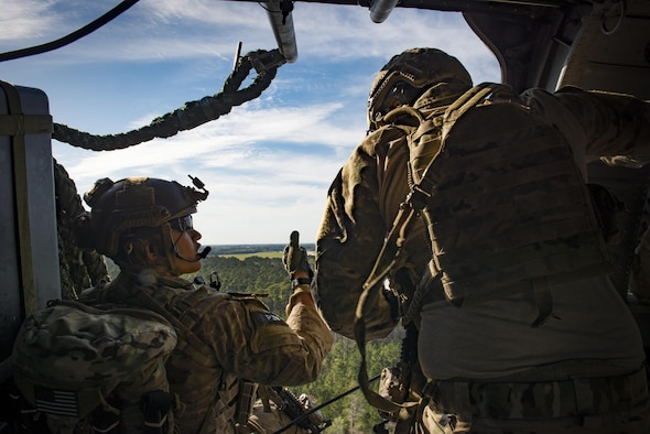 Pararescuemen from the 38th Rescue Squadron prepare to fast-rope from an HH-60G Pave Hawk as part of a combat search and rescue demonstration during the 75th Anniversary Flying Tiger Reunion, March 10, 2017, at Moody Air Force Base, Ga. In 1941, President Roosevelt signed an executive order forming the American Volunteer Group. The AVG was organized into the 1st, 2nd, and 3rd Pursuit Squadrons and later disbanded and replaced by the 23d Fighter Group in 1942. Under the command of Gen. Claire Chennault, the Flying Tigers comprised of the 74th, 75th, and 76th Pursuit Squadrons defended China against the Japanese. Throughout World War II, the Flying Tigers achieved combat success and flew the US-made Curtiss P-40 Warhawks painted with the shark-mouth design. (U.S. Air Force photo by Staff Sgt. Ryan Callaghan)