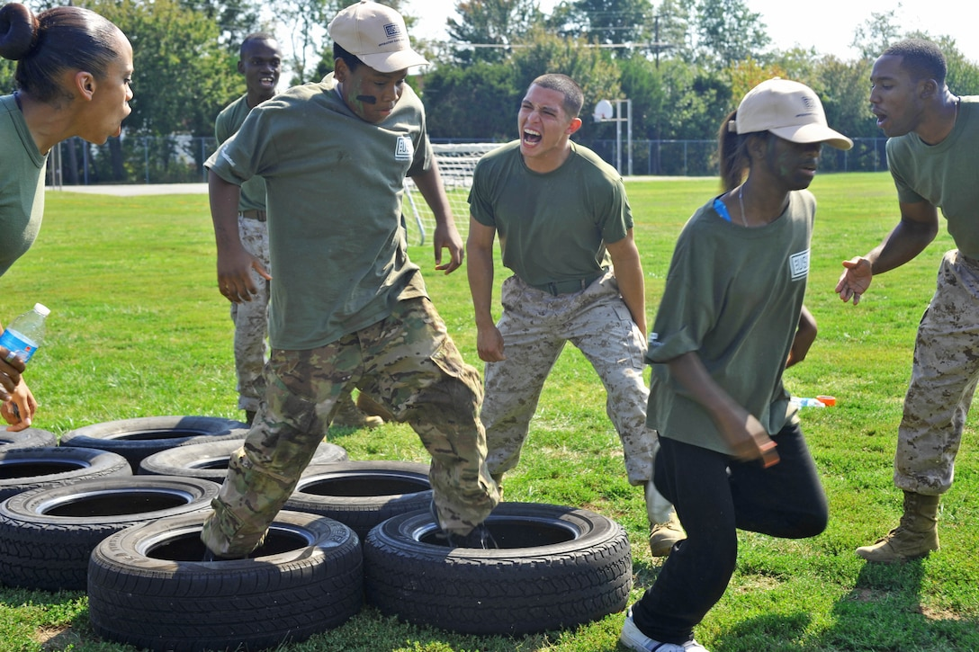 Teenagers run through tires in a simulated combat course.