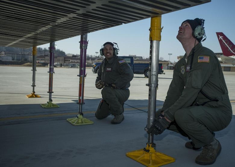 Staff Sgt. Jarryd Morgan, left, and Staff Sgt. Matthew Larson, assigned to the Airlift Squadron, set support jacks for a C-5M Super Galaxy in preparation to offload cargo through the forward ramp doors March 7, 2017 at Osan Air Base, South Korea. While at Osan AB, the loadmasters offloaded nearly 70,000 pounds of cargo. (U.S. Air Force photo by Staff Sgt. Nicole Leidholm)