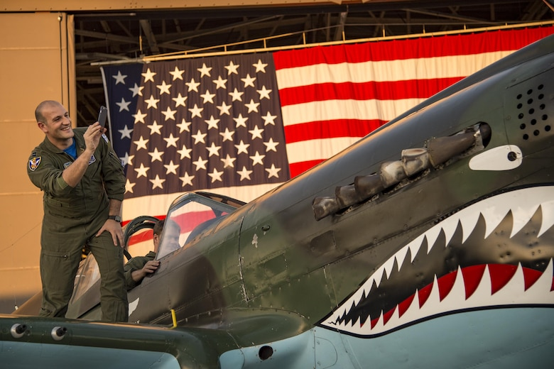 Capt. Roberto Manzo, 74th Fighter Squadron Italian Air Force exchange pilot, takes a photo of the Curtiss P-40 Warhawk static display during the 75th Anniversary Flying Tiger Reunion, March 10, 2017, at Moody Air Force Base, Ga. In 1941, President Roosevelt signed an executive order forming the American Volunteer Group. The AVG was organized into the 1st, 2nd, and 3rd Pursuit Squadrons and later disbanded and replaced by the 23d Fighter Group in 1942. Under the command of Gen. Claire Chennault, the Flying Tigers comprised of the 74th, 75th, and 76th Pursuit Squadrons defended China against the Japanese. Throughout World War II, the Flying Tigers achieved combat success and flew the US-made Curtiss P-40 Warhawks painted with the shark-mouth design. (U.S. Air Force photo by Andrea Jenkins)