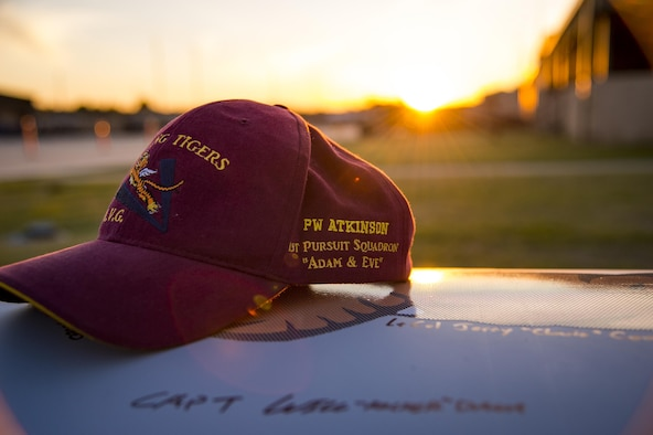 A hat adorned with the name and squadron of a deceased American Volunteer Group member rests on a decorative A-10C Thunderbolt II engine cover during the 75th Anniversary Flying Tiger Reunion, March 10, 2017, at Moody Air Force Base, Ga. In 1941, President Roosevelt signed an executive order forming the American Volunteer Group. The AVG was organized into the 1st, 2nd, and 3rd Pursuit Squadrons and later disbanded and replaced by the 23d Fighter Group in 1942. Under the command of Gen. Claire Chennault, the Flying Tigers comprised of the 74th, 75th, and 76th Pursuit Squadrons defended China against the Japanese. Throughout World War II, the Flying Tigers achieved combat success and flew the US-made Curtiss P-40 Warhawks painted with the shark-mouth design. (U.S. Air Force photo by Andrea Jenkins)