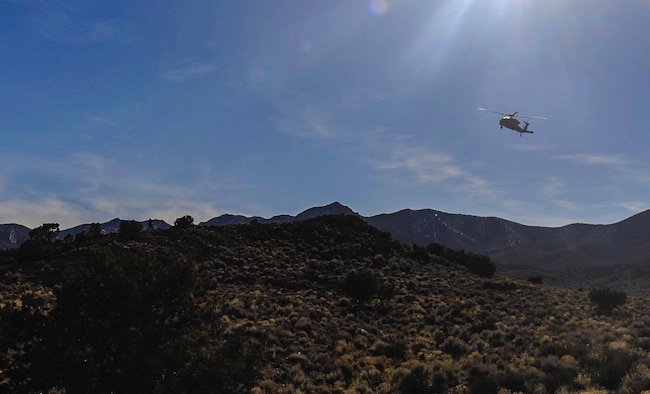 A Navy UH-60 Blackhawk flies over the Nevada Test and Training Range, looking for a downed pilot during a Red Flag 17-2 combat search and rescue mission, March 8, 2017. A CSAR mission may be carried out by a task force of helicopters, ground-attack aircraft, aerial refueling tankers and an airborne command post. (U.S. Air Force photo by Airman 1st Class Kevin Tanenbaum/Released)
