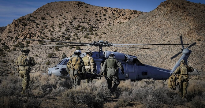 Pararescuemen carry a simulated downed pilot to a U.S. Navy UH-60 Blackhawk during a Red Flag 17-2 combat search and rescue mission on the Nevada Test and Training Range, March 8, 2017. The mission of pararescue is to rescue, recover, and return American or Allied forces in times of danger or extreme duress. (U.S. Air Force photo by Airman 1st Class Kevin Tanenbaum/Released)