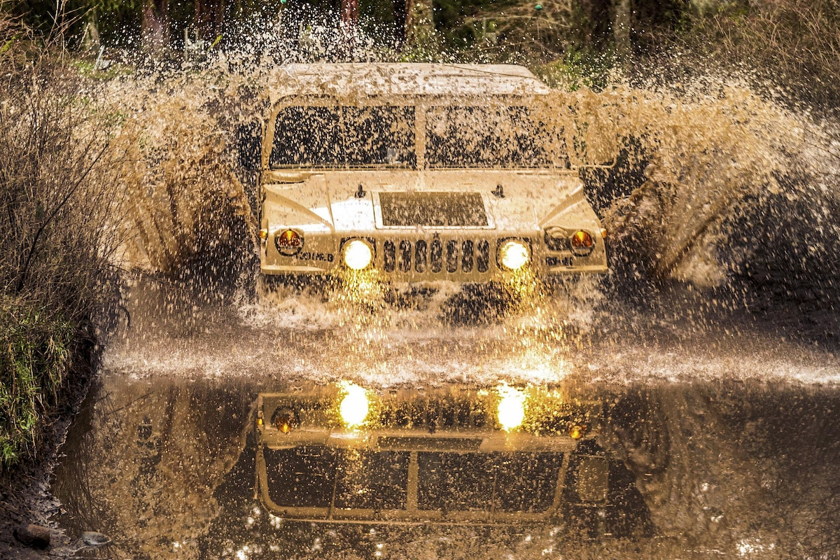 Soldiers maneuver a Humvee through a water obstacle.