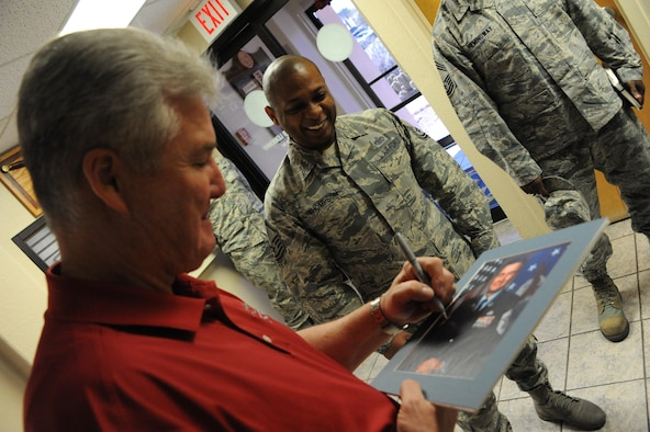 Master Sgt. Bruce Thompson, 56th Force Support Squadron Airmen Leadership School commandant, watches as Retired Chief Master Sgt. of the Air Force Gerald Murray autographs his last official photo from over 10 years ago on March 10, 2017, at Luke Air Force Base, Ariz. Murray visited several different agencies around Luke and was the guest speaker for the Maintenance Professional of the Year event which took place March 11, 2017. (U.S. Air Force photo by Airman 1st Class Caleb Worpel)