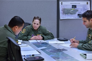 Puerto Rico Air National Guard Maj. Isbelia Reyes, center, an aircraft commander assigned to the 156th Airlift Wing, briefs Capts. Jesuan Aviles, left, and Mario Ibarra before participating in a mission to commemorate International Women's Day at Muñiz Air National Guard Base, Puerto Rico, March 8, 2017. Aviles is a navigator and Ibarra is a pilot assigned to the wing. Air National Guard photo by Staff Sgt. Angel Oquendo