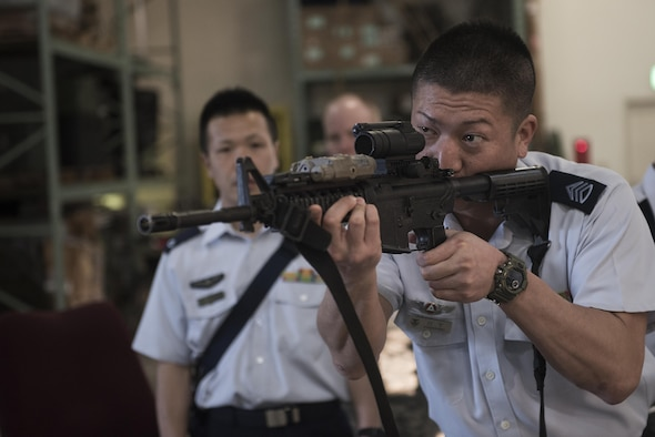 Members of the Japan Air Self-Defense Force learn about and handle different weapons during a tour of the Security Forces Squadron March. 14, 2017, at Kadena Air Base, Japan. They were then given a tour of the Squadron and its different sections, such as the base defense operations center, investigations office and interview and holding cells. (U.S. Air Force photo by Airman 1st Class Corey Pettis/Released)