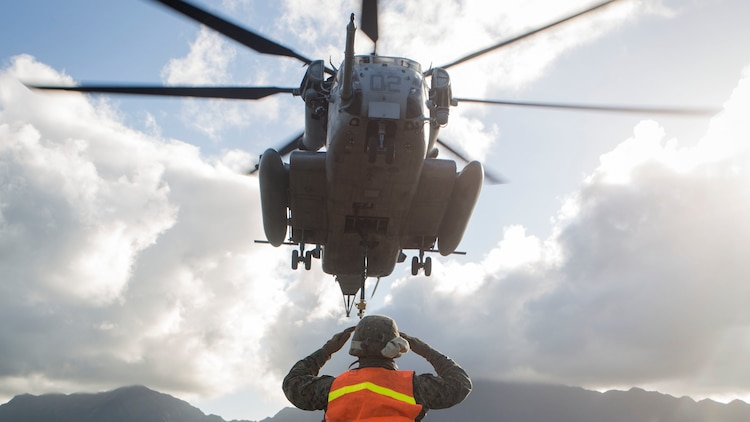 Pfc. Jose Camacho, a landing support specialist with Transportation Services Company, Combat Logistics Battalion 3, guides a CH-53E Super Stallion helicopter assigned to Marine Heavy Helicopter Squadron 463, during external lift training at Landing Zone West Field at Marine Corps Air Station Kaneohe Bay, Hawaii, March 8, 2017. This training improves proficiency for the pilots when moving supplies while Marines on the ground conditioned themselves to safely prepare dual and single load lifts.